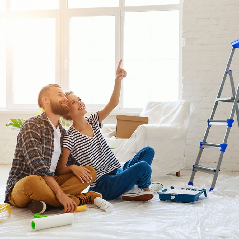 couple painting walls in their new home